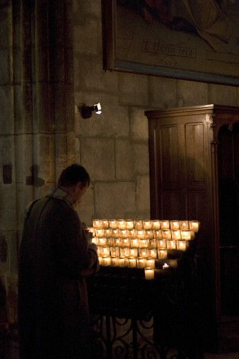 Paris, France; A man lighting a candle in a church : Stock Photo
