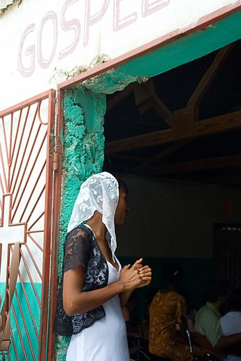 Haiti; Young woman standing in front of church door : Stock Photo