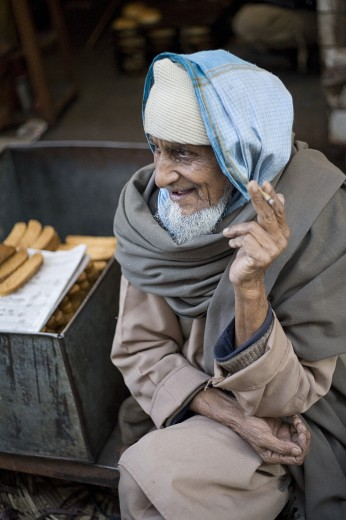 Old Delhi, India; Elderly man smoking : Stock Photo