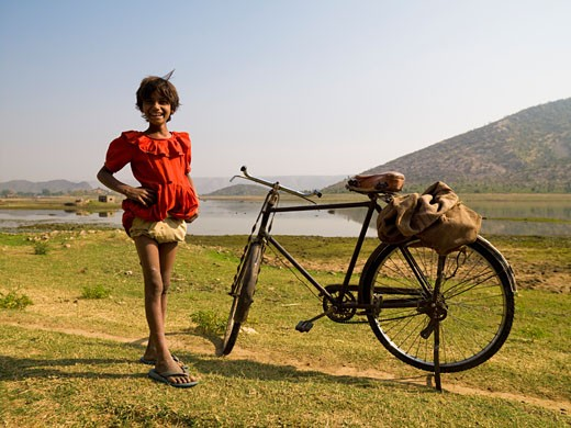 Rajasthan,India;Girl standing by a bicycle : Stock Photo