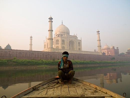 Taj Mahal,Agra,India;Man sitting on a boat by the Taj Mahal : Stock Photo