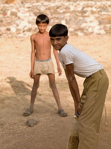 Aravalli Hills,Rajasthan,India;Two boys playing cricket,using makeshift equipment  : Stock Photo