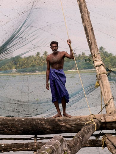 Kochi,Kerala,India;Fisherman stands alongside Chinese fishing nets : Stock Photo