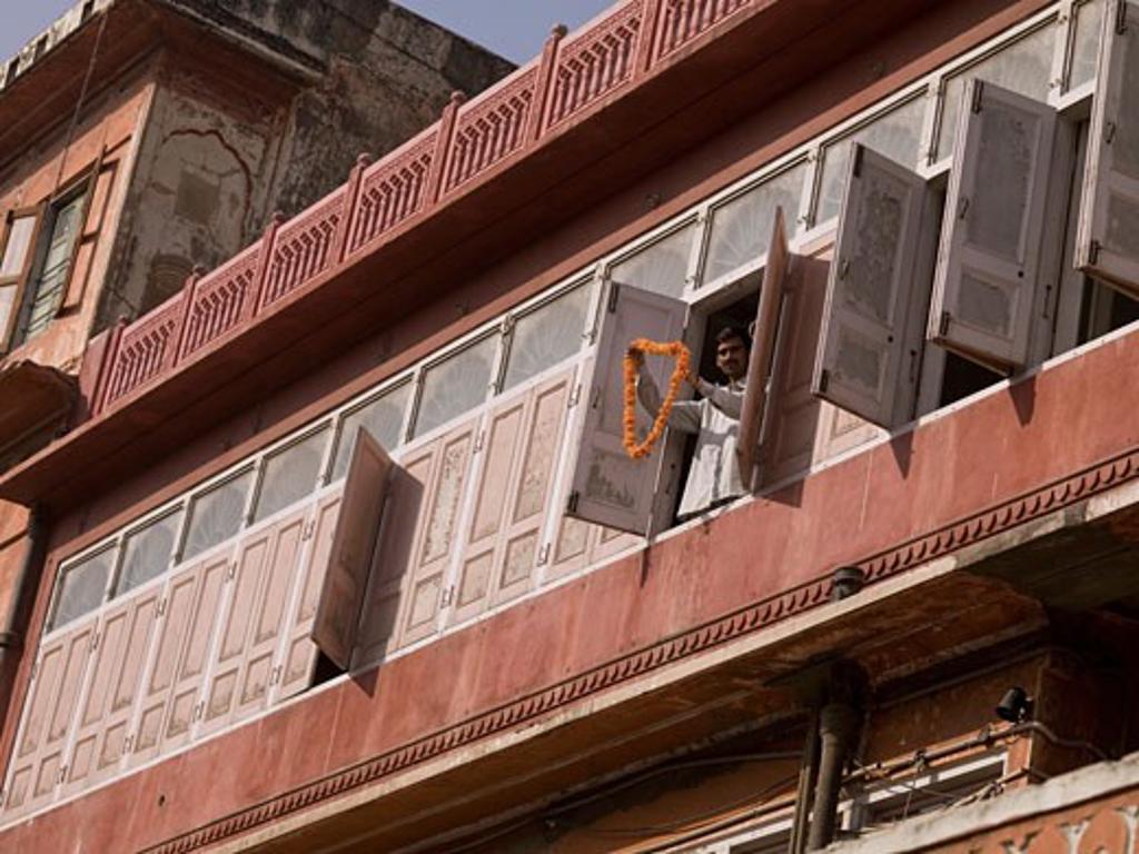 Jaipur,Rajasthan,India;Man standing at window,holding flower garland : Stock Photo