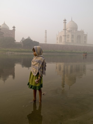 Stock Photo: 1889-44021 Taj Mahal,Agra,India;Portrait of young girl standing in the river,with the Taj Mahal behind her