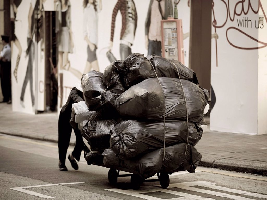 Person carting garbage bags down a street : Stock Photo