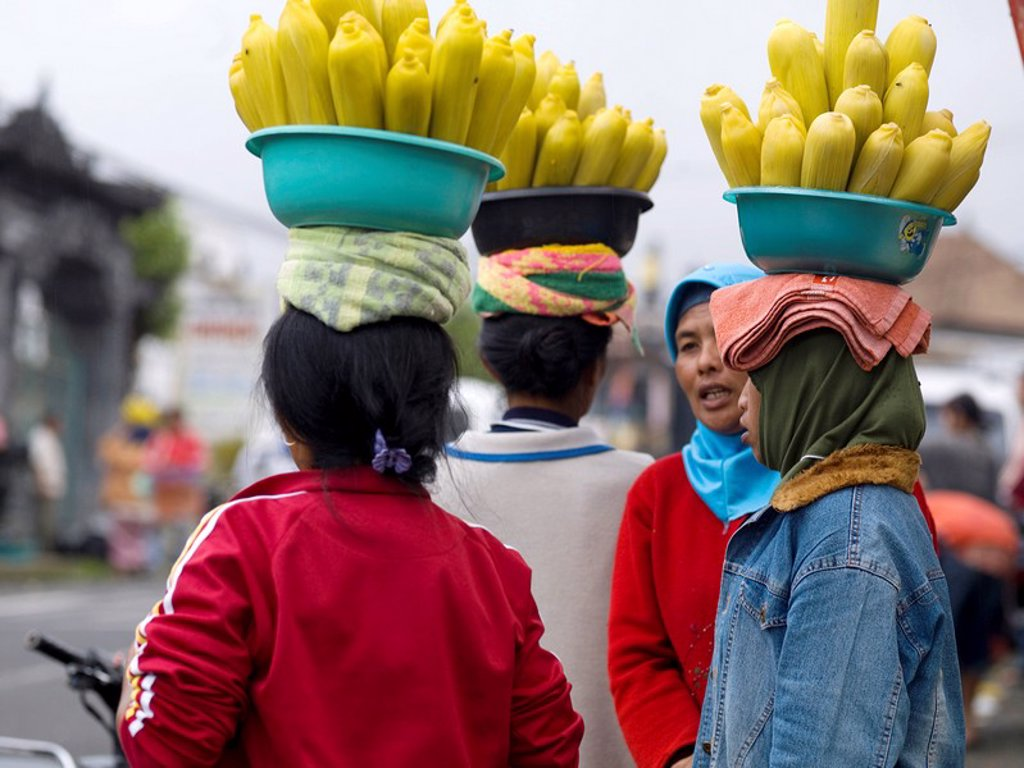 Women carrying bowls of corn on heads : Stock Photo