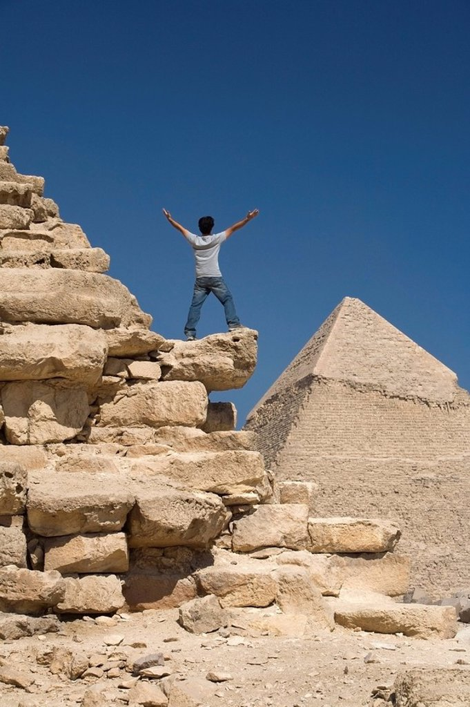 Stock Photo: 1889-44697 Man standing on part of a Pyramid in the desert