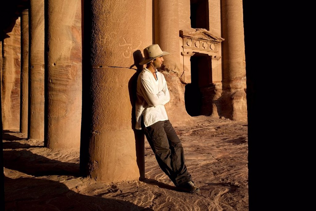 Stock Photo: 1889-44763 Man standing by royal tomb in Petra