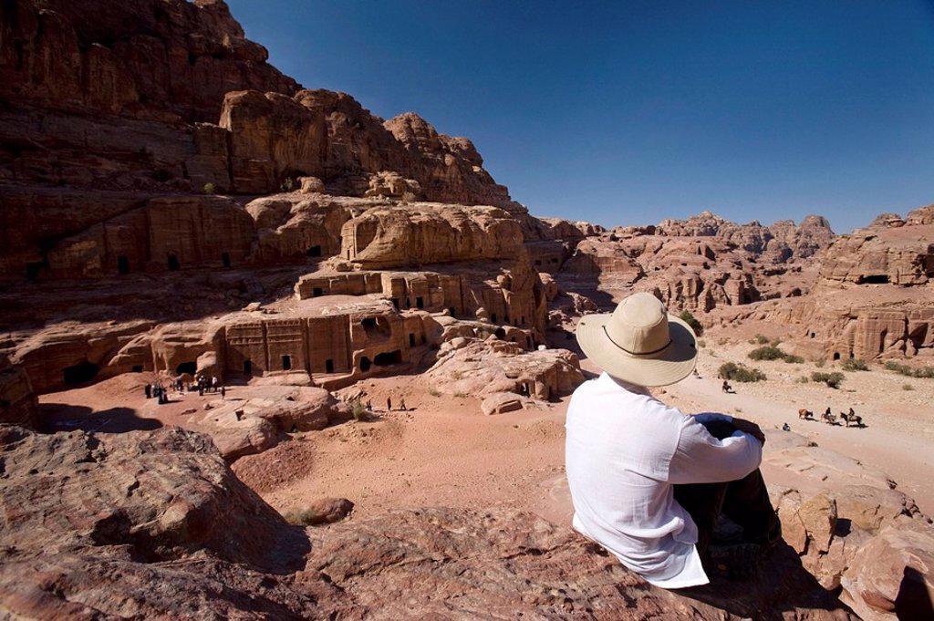 Stock Photo: 1889-44770 Man sitting near monumental Nabataean tombs