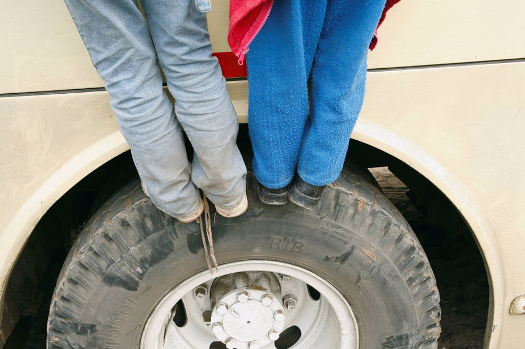 Two children standing on car tire, Lima, Peru : Stock Photo