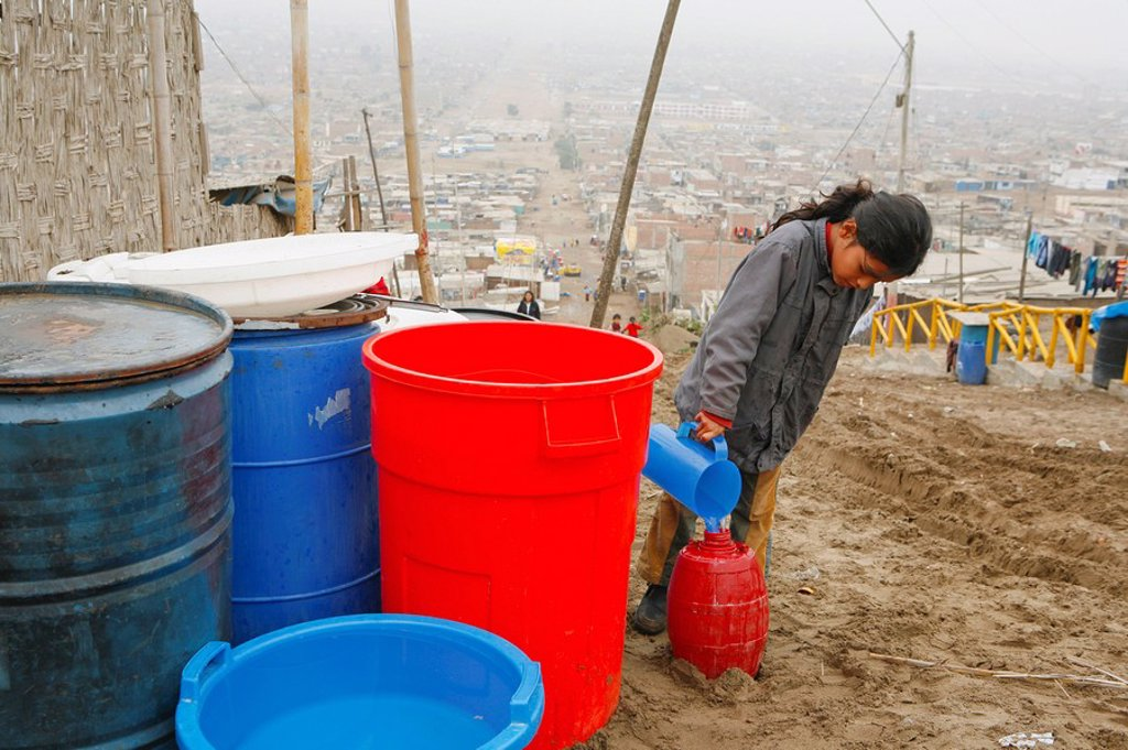 Young girl pouring water into bucket, Lima, Peru : Stock Photo