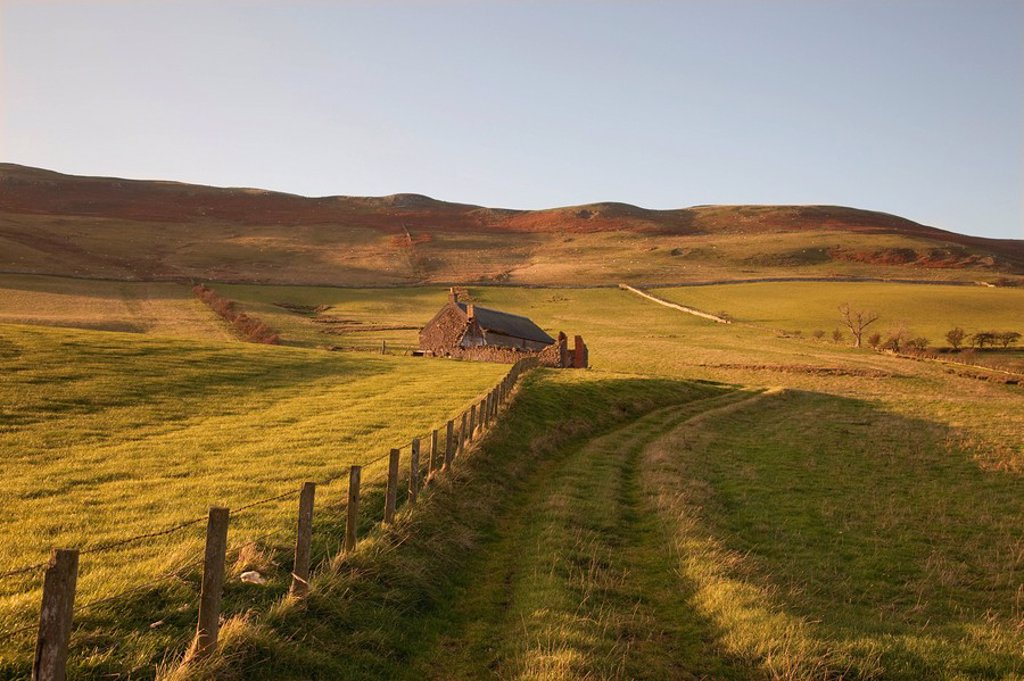 northumberland, england, a farm structure and a fence around a field : Stock Photo