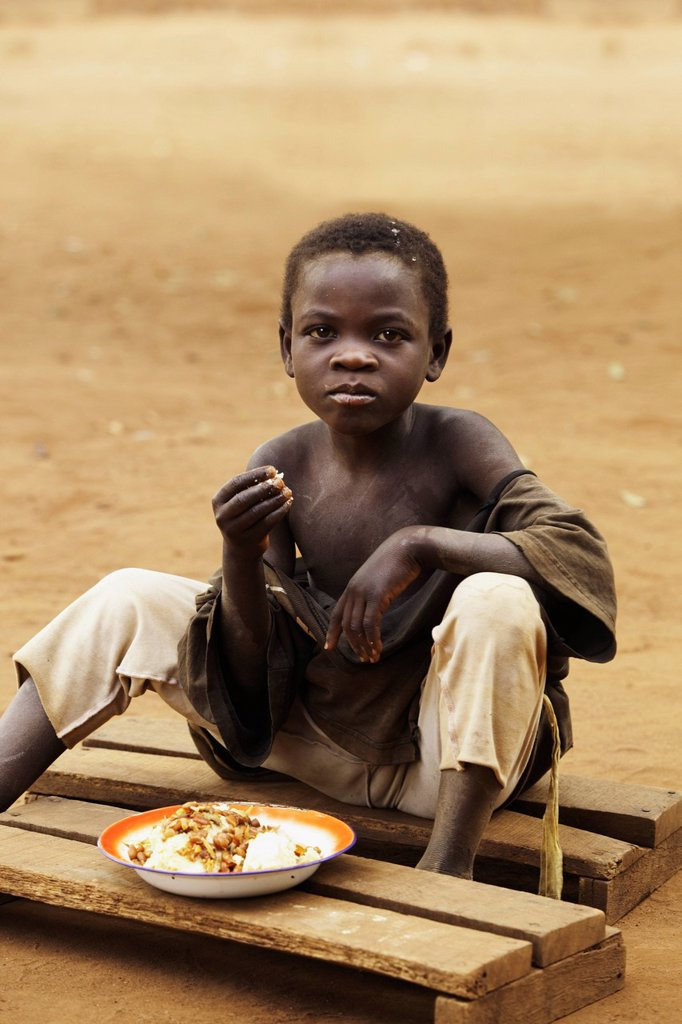 A Boy Eats A Meal Sitting On Boards On The Ground, Manica, Mozambique, Africa : Stock Photo