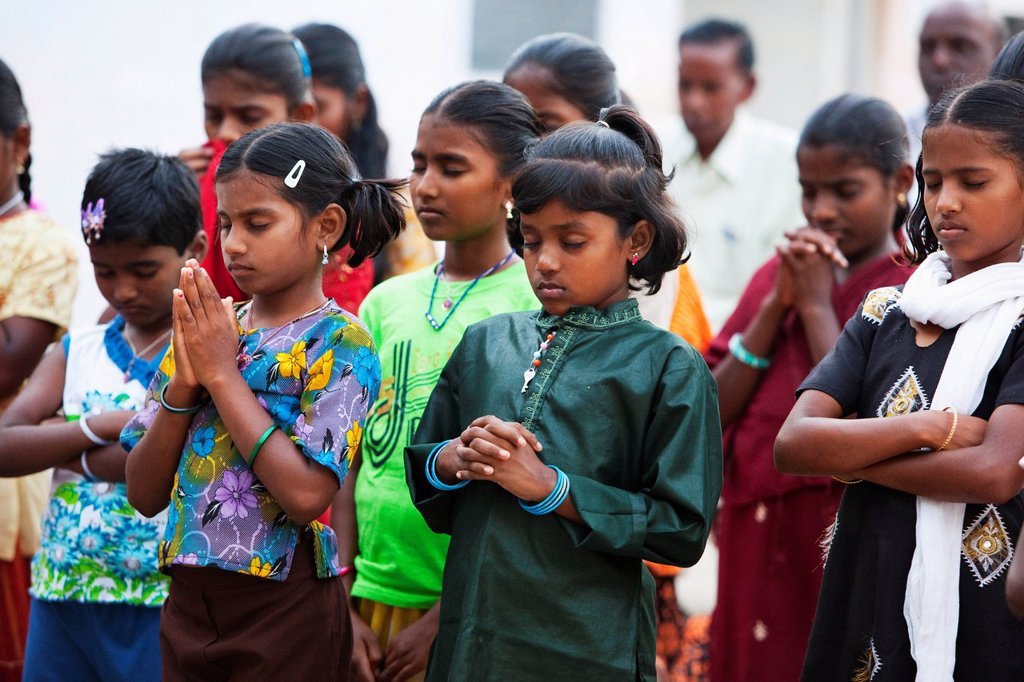Stock Photo: 1889-57414 girls standing in rows with eyes closed in prayer with men standing in the background, sathyamangalam, tamil nadu, india