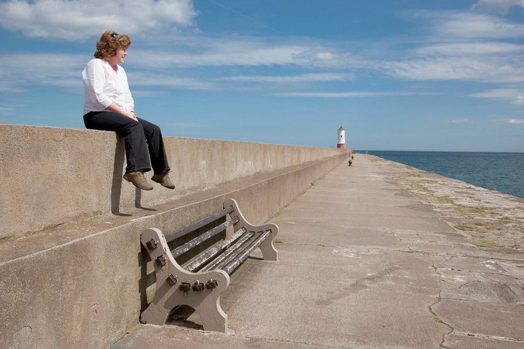 Woman looking out at the water : Stock Photo