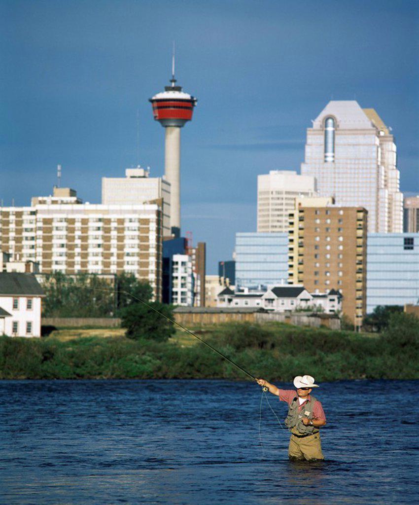 Stock Photo: 1889-59132 Man fishing in the Bow river, Calgary, Alberta, Canada