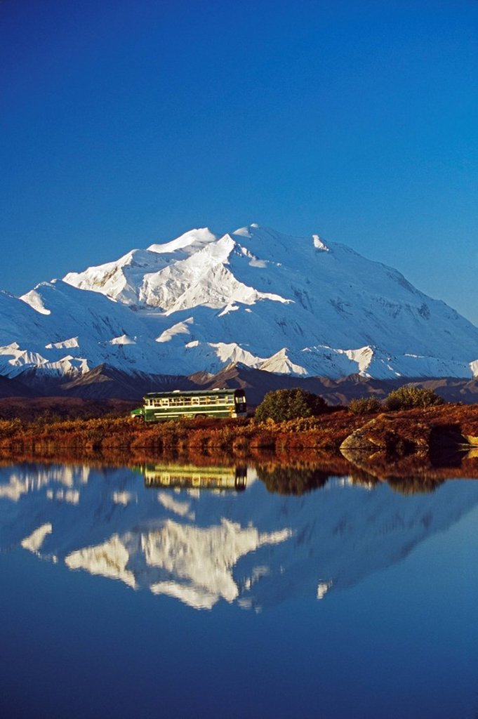 Visitor bus passes along tundra pond with reflection of Mount McKinley, Alaska : Stock Photo