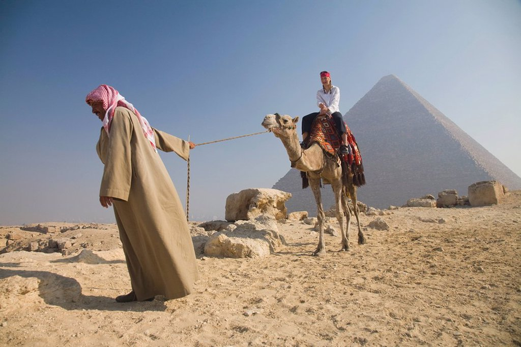 Young woman tourist riding a camel lead by a guide at the Pyramids of Giza, Egypt : Stock Photo