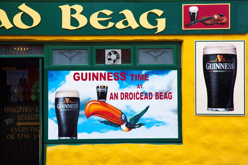 exterior of pub with signs depicting guinness ale, dingle, county kerry, ireland : Stock Photo