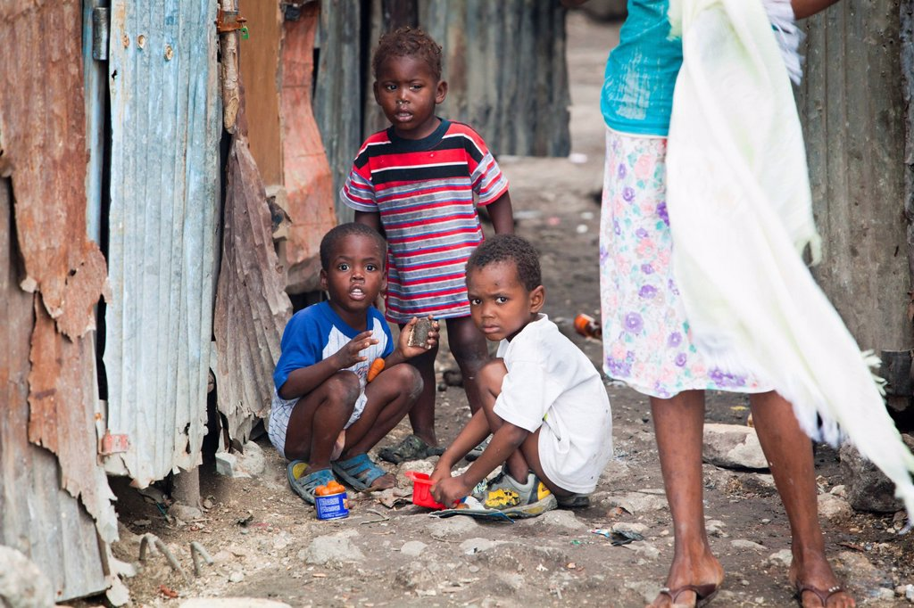 a woman standing with three young boys as they play outside, port_au_prince, haiti : Stock Photo