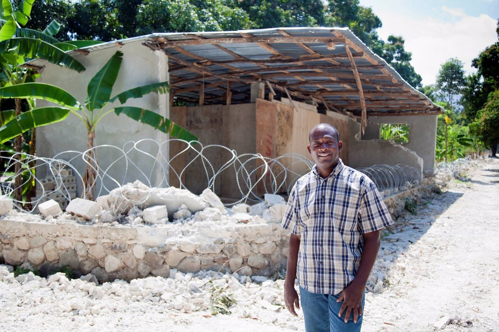 Stock Photo: 1889-63381 a man stands in front of ruins and a barbed wire sitting on top of what was a compound wall, grand goave, haiti