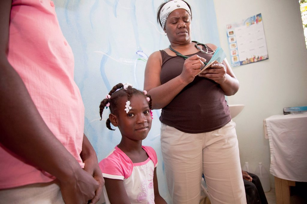 a nurse seeing young haitian patients at a clinic, grand saline, haiti : Stock Photo
