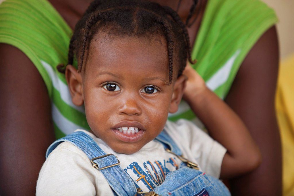 a young girl held in an adult´s arms, grand saline, haiti : Stock Photo