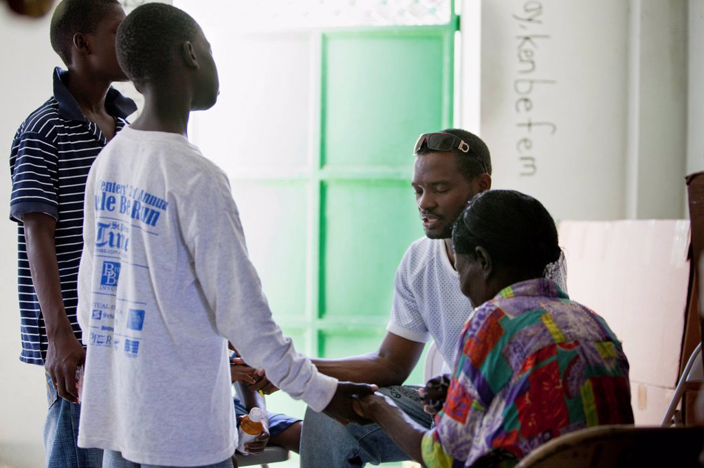 a group of people holding hands in prayer at the hope alive medical clinic, grand saline, haiti : Stock Photo