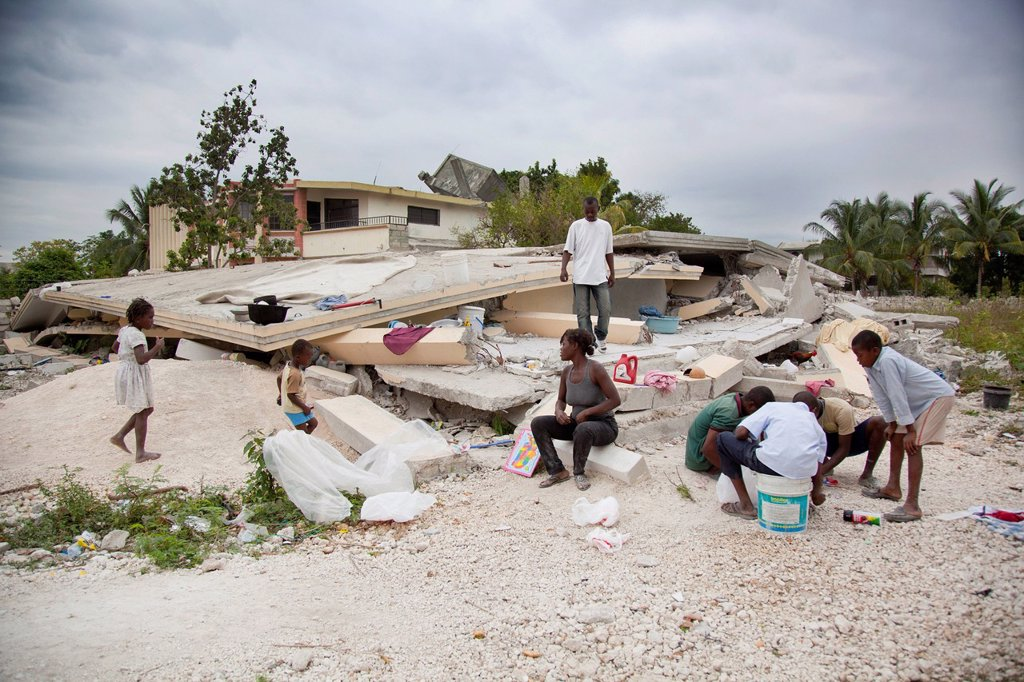 a family sits amidst the rubble of their home, port_au_prince, haiti : Stock Photo