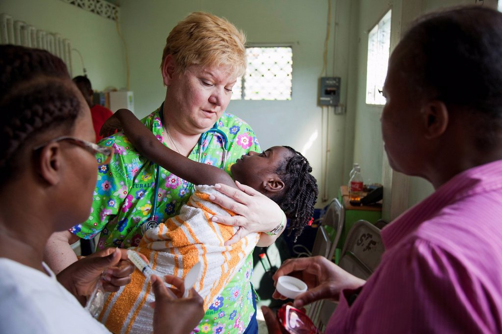 a volunteer nurse cares for a child that suffers from seizures, grand saline, haiti : Stock Photo