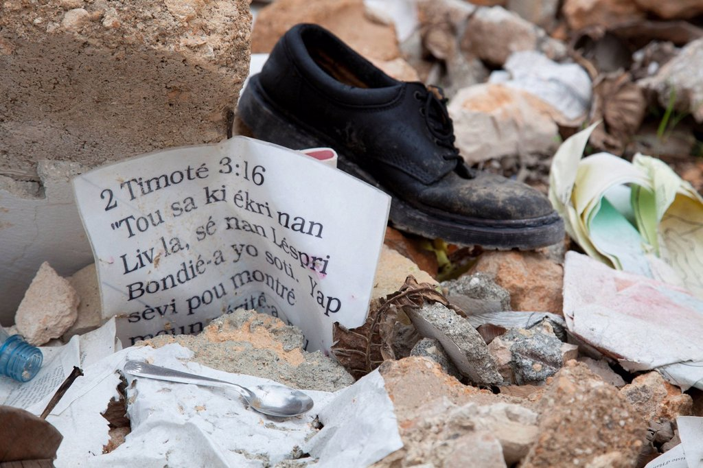 Stock Photo: 1889-63433 a bible verse 2 timothy 3:16 laying in the ruins after the haiti earthquake, port_au_prince, haiti