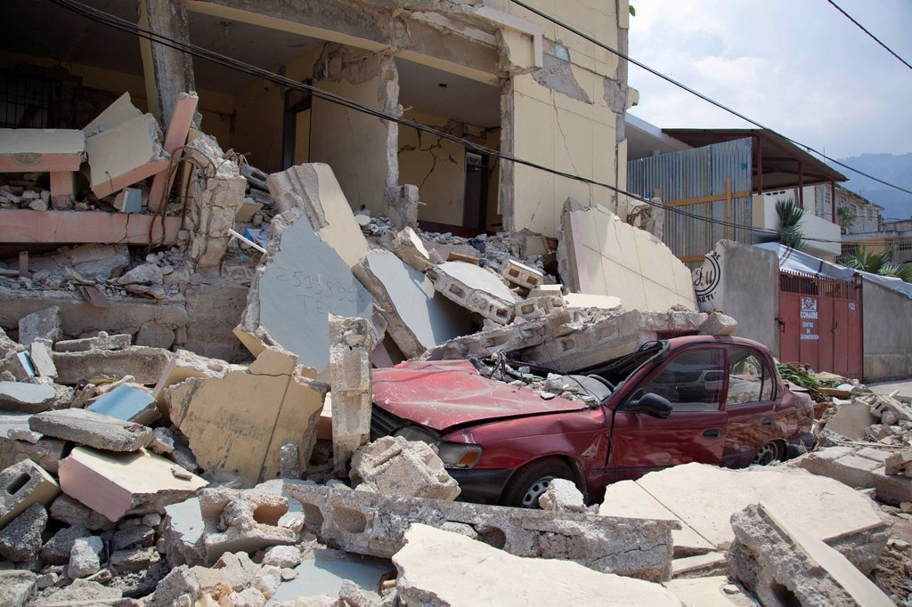 a car is crushed when a building collapses after the earthquake, port_au_prince, haiti : Stock Photo