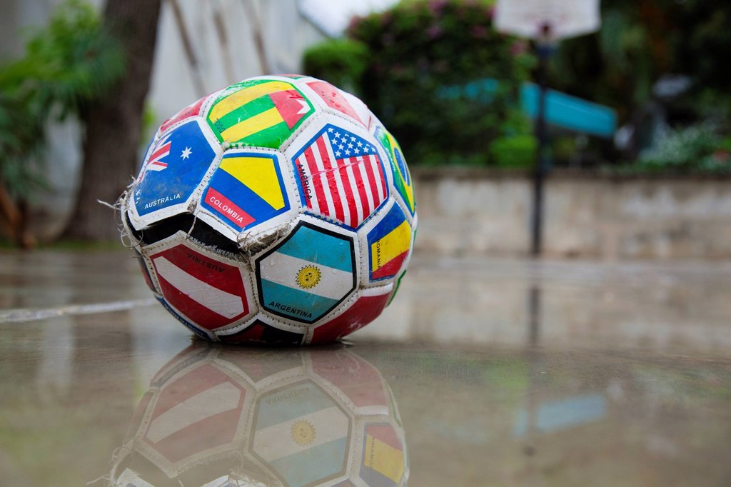 a soccer ball marked with various flags is ripped and sitting in water, port_au_prince, haiti : Stock Photo