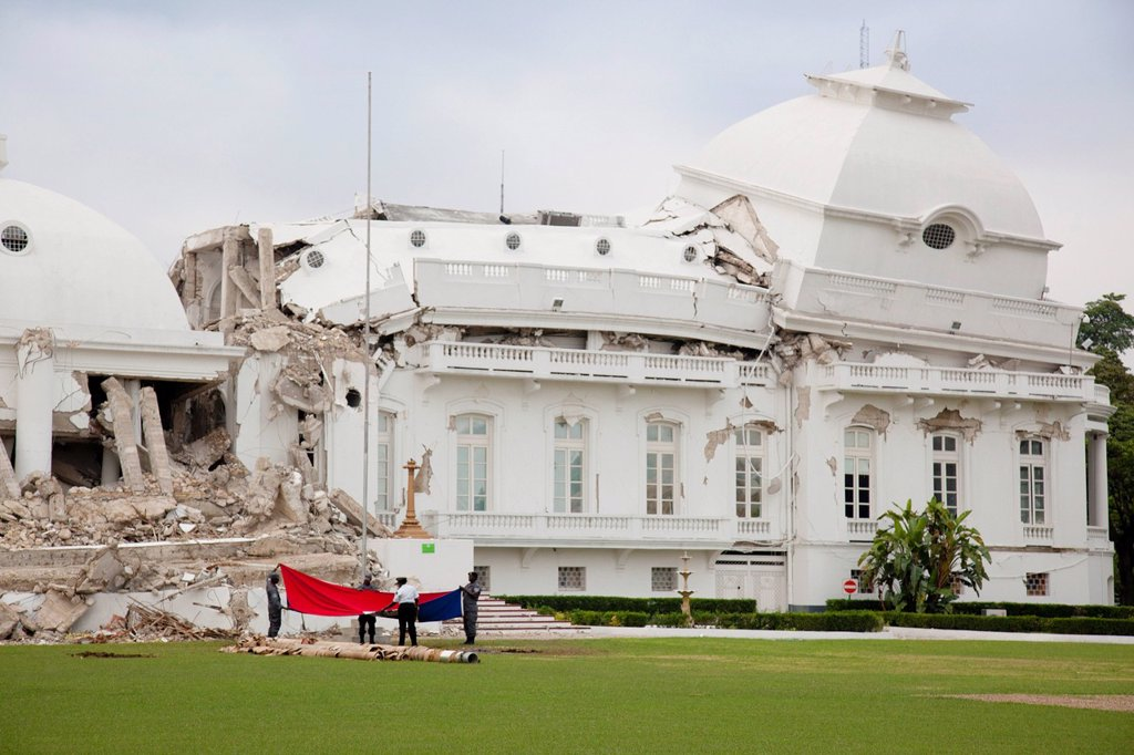 the presidential palace government building leans and is collapsed and the flag is being removed from the pole after the earthquake, port_au_prince, haiti : Stock Photo
