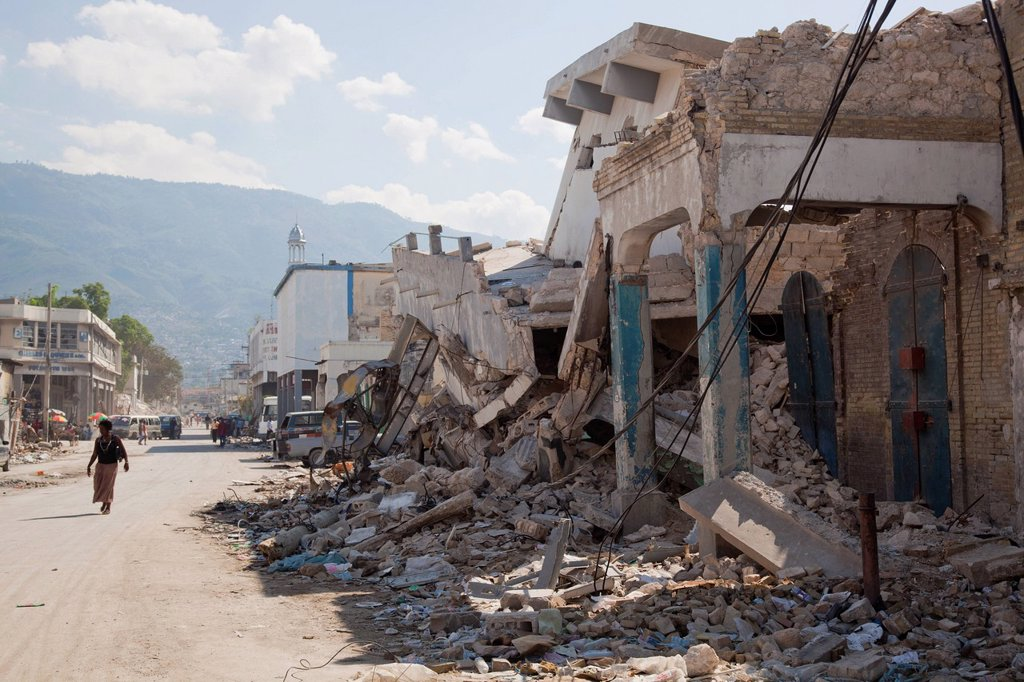Stock Photo: 1889-63526 a person walks down the street beside collapsed buildings after the earthquake, port_au_prince, haiti