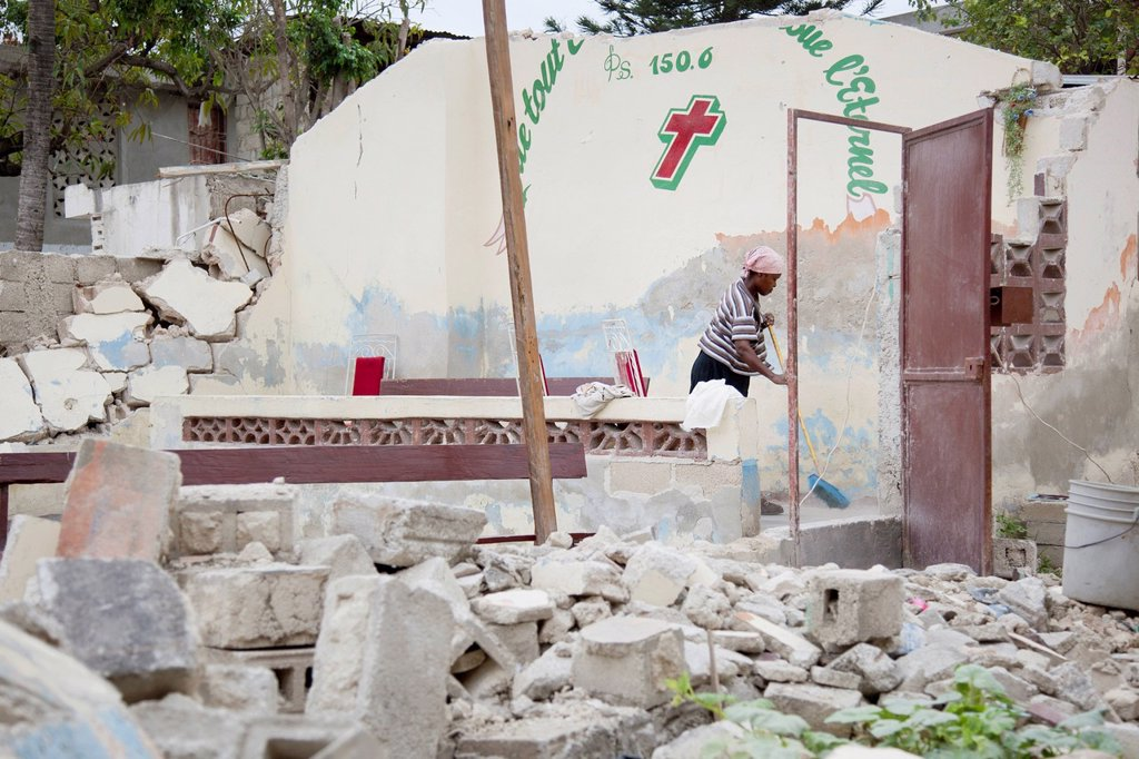 a woman cleans up around the rubble of a destroyed church building after the earthquake, port_au_prince, haiti : Stock Photo