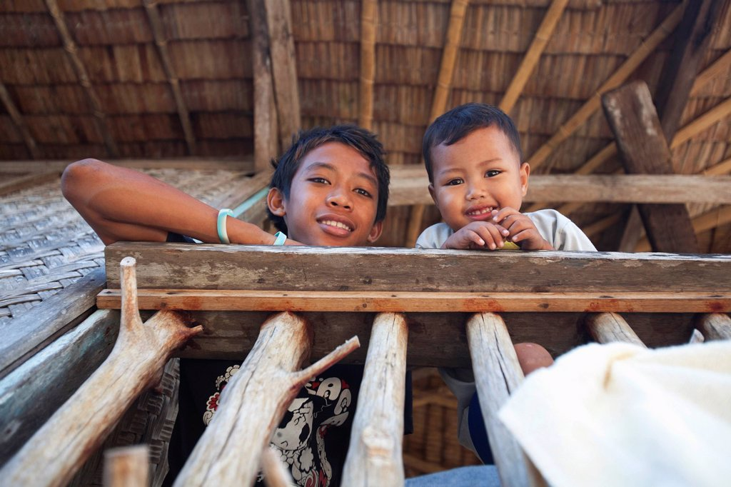 two children smile in the remote and tiny fishing village of vigan near snake island and el nido, vigan, bacuit archipelago, palawan, philippines : Stock Photo