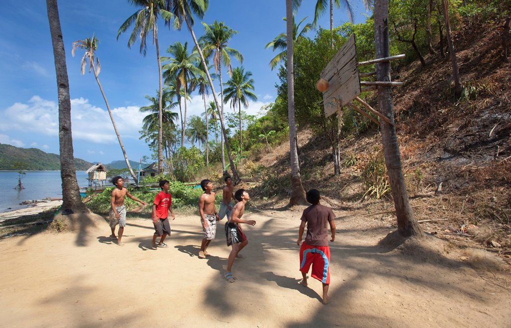 a group of teenage boys play basketball with the hoop attached to a coconut tree in the tiny fishing village of vigan near snake island and el nido, vigan, bacuit archipelago, palawan, philippines : Stock Photo