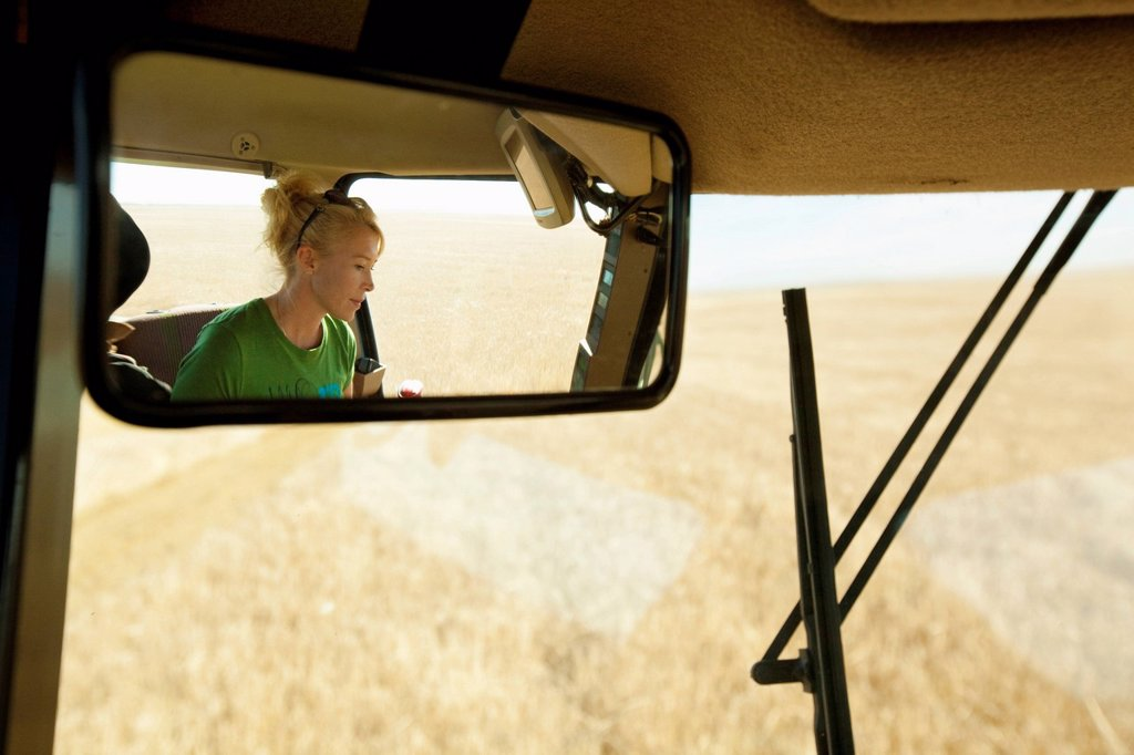 female farmer in combine seen in rear_view mirror, three hills, alberta, canada : Stock Photo