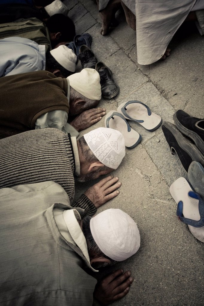 Men Wearing Prayer Caps And Bowing In Prayer, Srinagar Kashmir India : Stock Photo