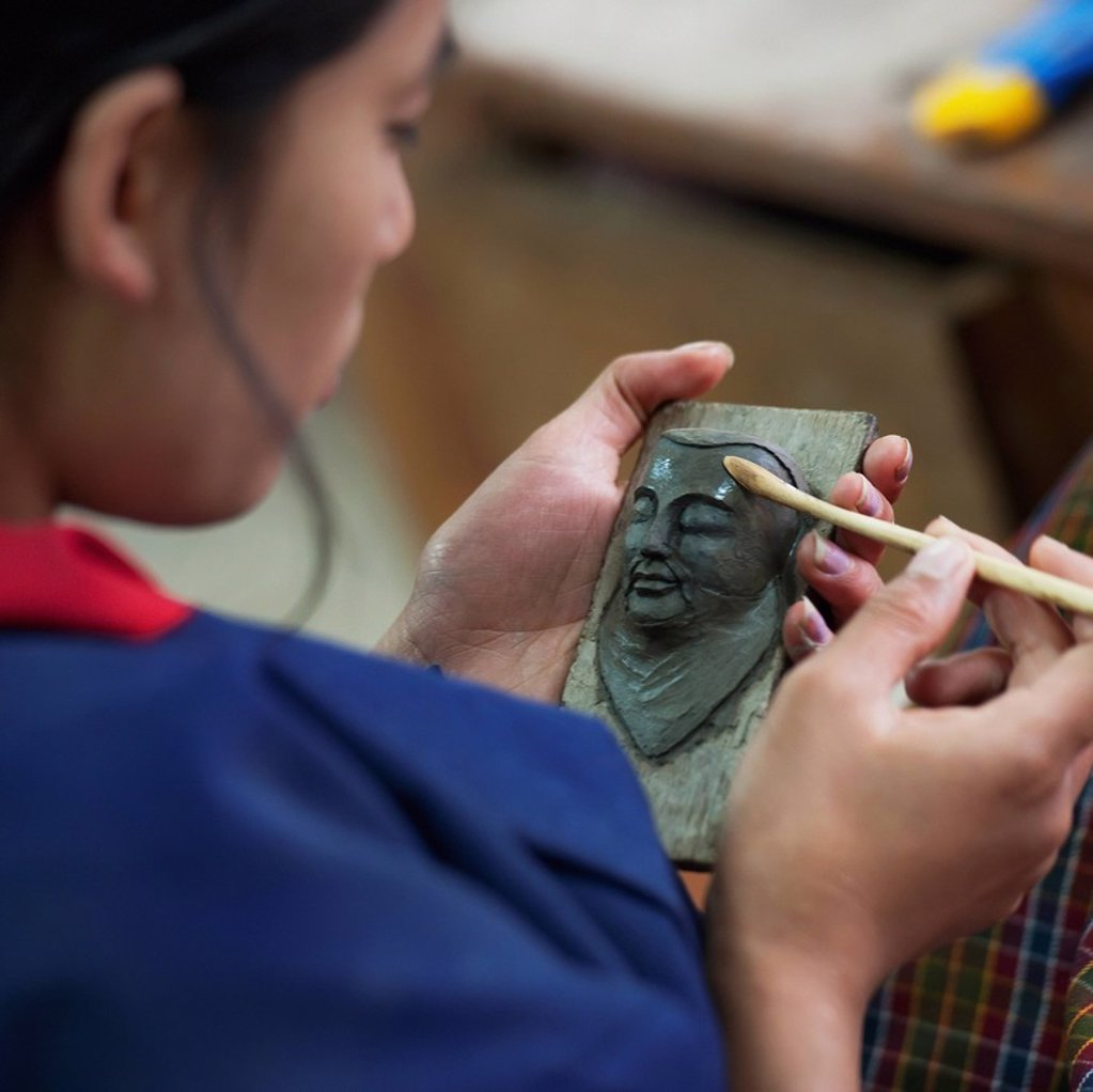 Stock Photo: 1889-65960 A Woman Works On A Sculpture Of A Human Face, Thimphu Thimphu District Bhutan