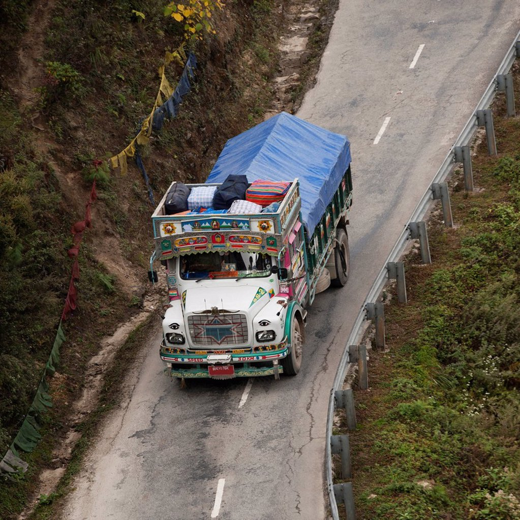 a truck covered with a tarp traveling on a road, thimphu district bhutan : Stock Photo