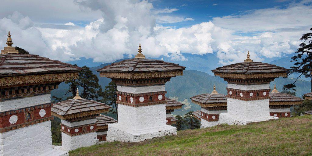 white ornate pillars on the side of a mountain, thimphu district bhutan : Stock Photo