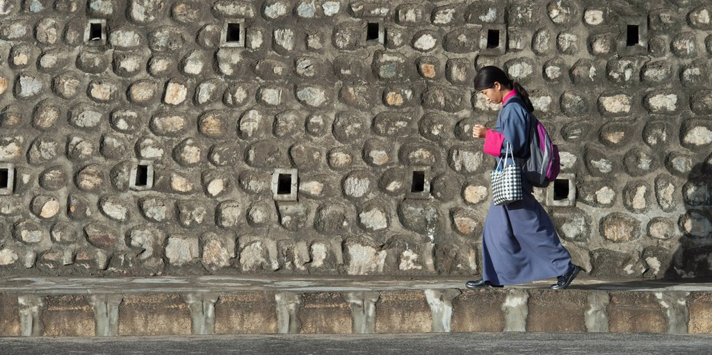 Stock Photo: 1889-66715 Woman Walking By Stone Building, Thimphu Bhutan