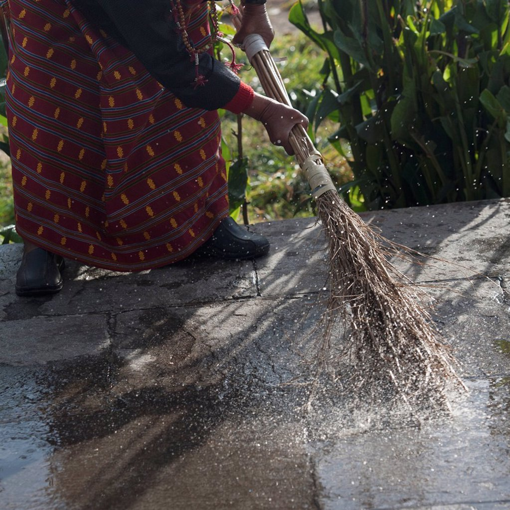 Woman Sweeping Water Off The Memorial Chorten, Thimphu Bhutan : Stock Photo