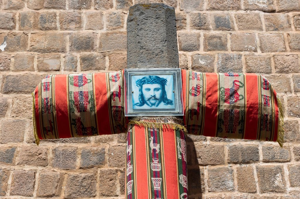 Stock Photo: 1889-66759 A Picture Of Jesus Christ On A Fabric Covered Cross Against A Brick Wall, Cusco Peru