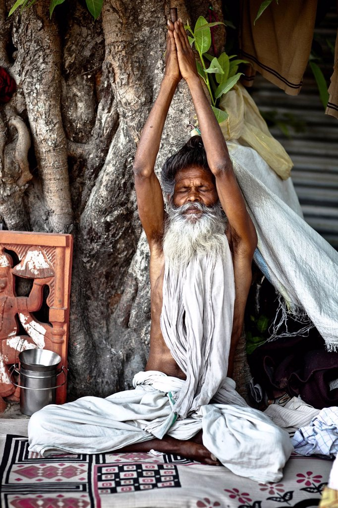 Stock Photo: 1889-66893 A Holy Man Sits With Eyes Closed And Arms Raised, Haridwar India