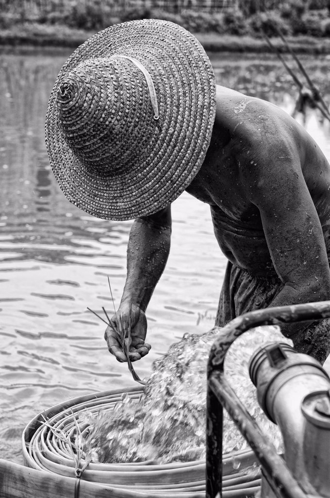 Stock Photo: 1889-72691 a man washing from the water pouring out of a pipe, ruili yunnan china