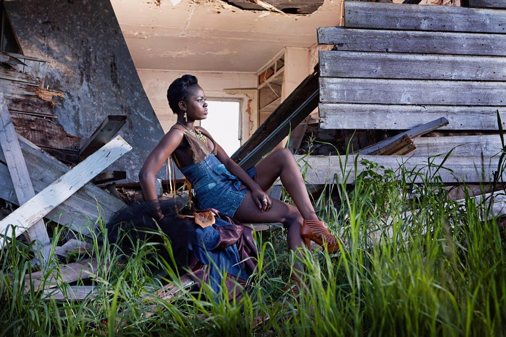 a young woman sits at the back of a dilapidated house, leduc, alberta, canada : Stock Photo